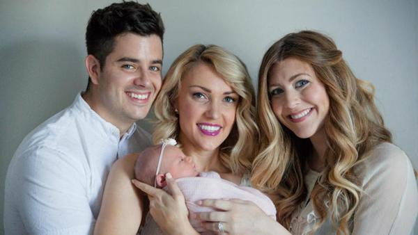 Vợ chồng Amanda hạnh phúc bế con gái Adalyn do chính em chồng Rachel (bên phải) mang thai và sinh hộ. Ảnh: PA Real Life