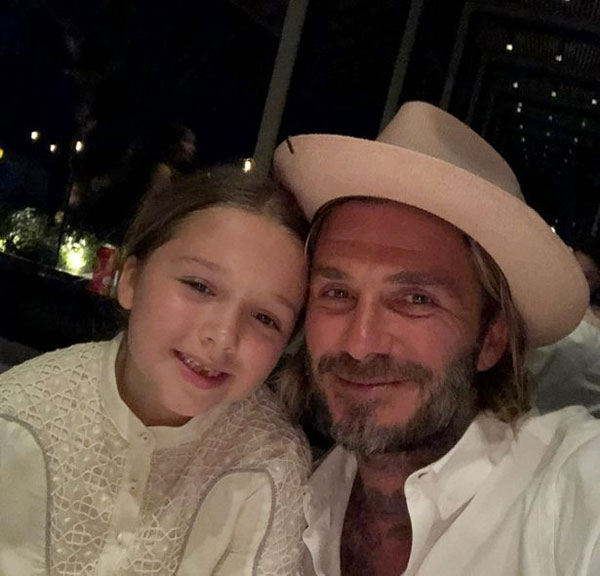 Becks vẫn đội mũ chụp ảnh cùng cô con gái cưng Harper trong khung cảnh buổi tối giao thừa. Hai bố con cựu danh thủ Anh đều mặc đồ trắng.