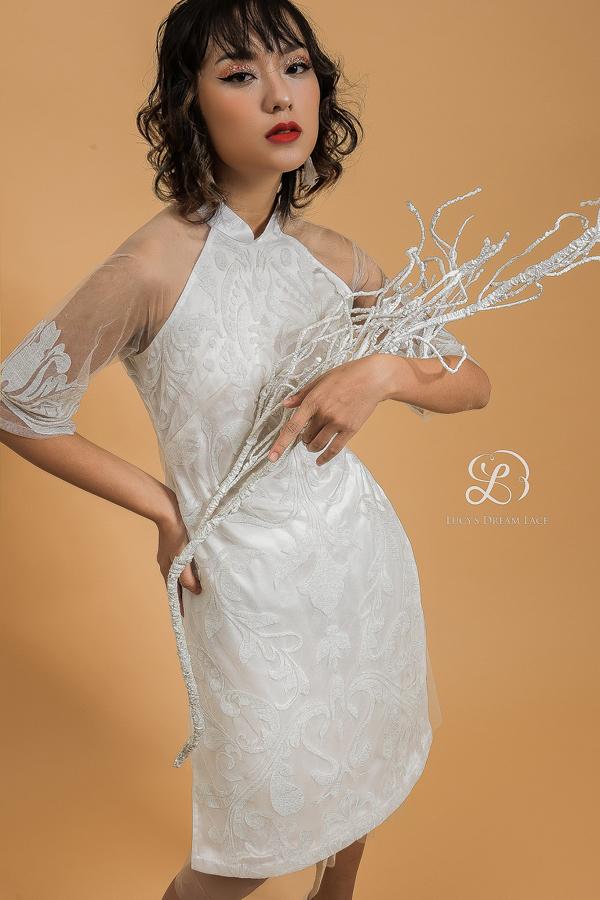 Áo dài cách tân ren kim tuyến, với hoa văn ren lấy cảm hứng từ kiến trúc thời kỳ Phục Hưng. Nếu yêu thích thiết kế, khách hàng có thể đặt may theo số đo,thay đổi độ dài của trang phục,biến áo dài thành váy liền.