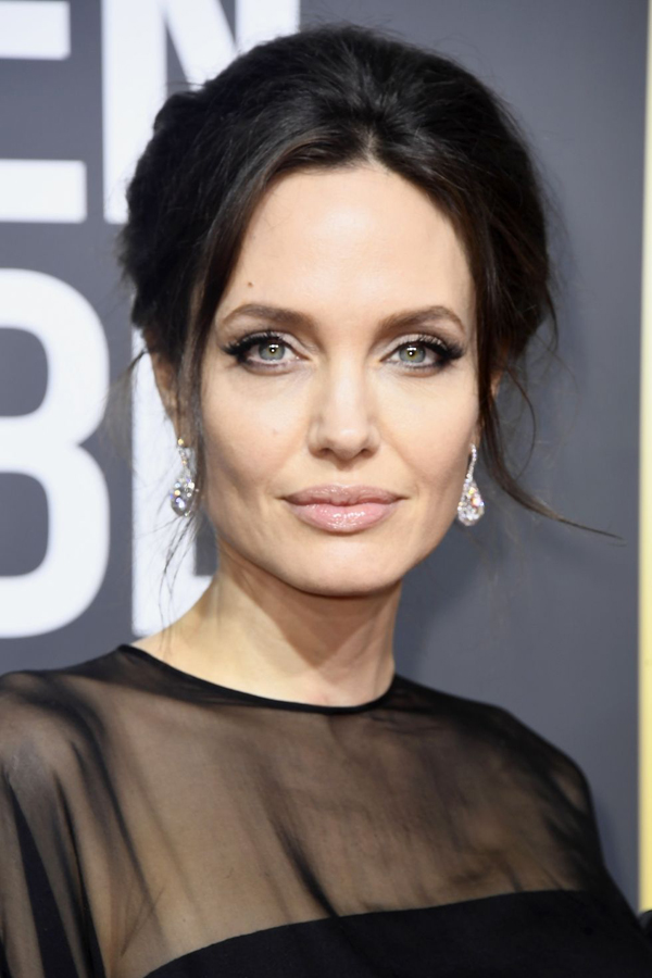 Angelina Jolie trung thành với kiểu trang điểm quen thuộc nhiều năm nay: son môi màu nude và mắt khói xám đen.
