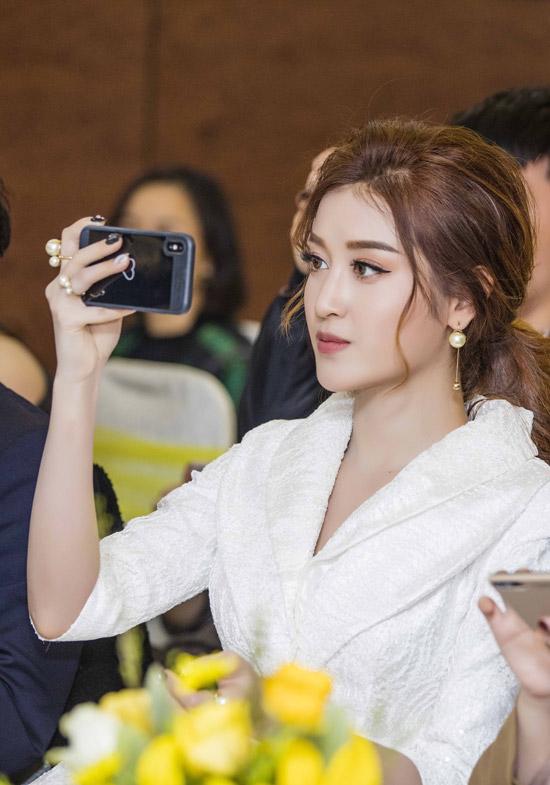 Trên hàng ghế khách mời, Huyền My chăm chú dùng điện thoại để chụp hình và quay video các hoạt động trên sân khấu.