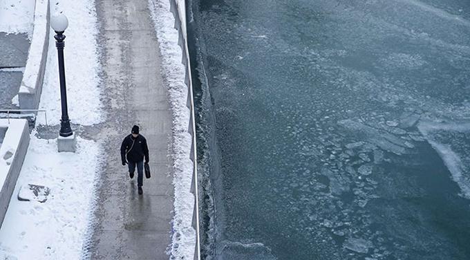Người đi bộ dọc sông Chicago, một bên phủ tuyết còn một bên dòng sông đã đóng băng do nhiệt độ xuống thấp.
