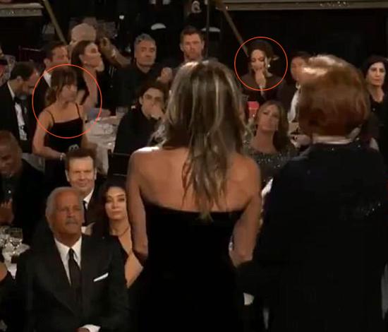 Người xem truyền hình đã bắt gặp khoảnh khắc bối rối của Angelina Jolie khi Jennifer Aniston (váy quây hở vai) lên trao giải Nữ diễn viên xuất sắc trong seri phim hài/ca nhạc. Angelina và cậu con trai Pax Thiên ngồi ngay gần sân khấu, bởi vậy cô và Jennifer có thể nhìn rõ nhau. Bà Smith chọn cách cúi mặt xuống bàn thưởng thức đồ ăn trong khi Jennifer phát biểu. Một số đồng nghiệp, trong đó có nữ diễn viên 27 tuổi Dakota Johnson (bên trái bức ảnh) đã tò mò quay sang nhìn phản ứng của Angelina Jolie.