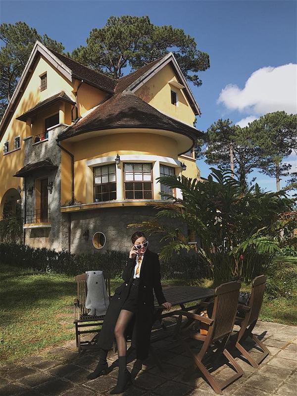 Sơ mi, kính gọng trái tim điệu đà tông màu trắng thanh nhã được ca sĩ Yến Nhi sử dụng để phối cùngset đồ đen gồm chân váy chữ A, áo choàng bốt cổ cao.