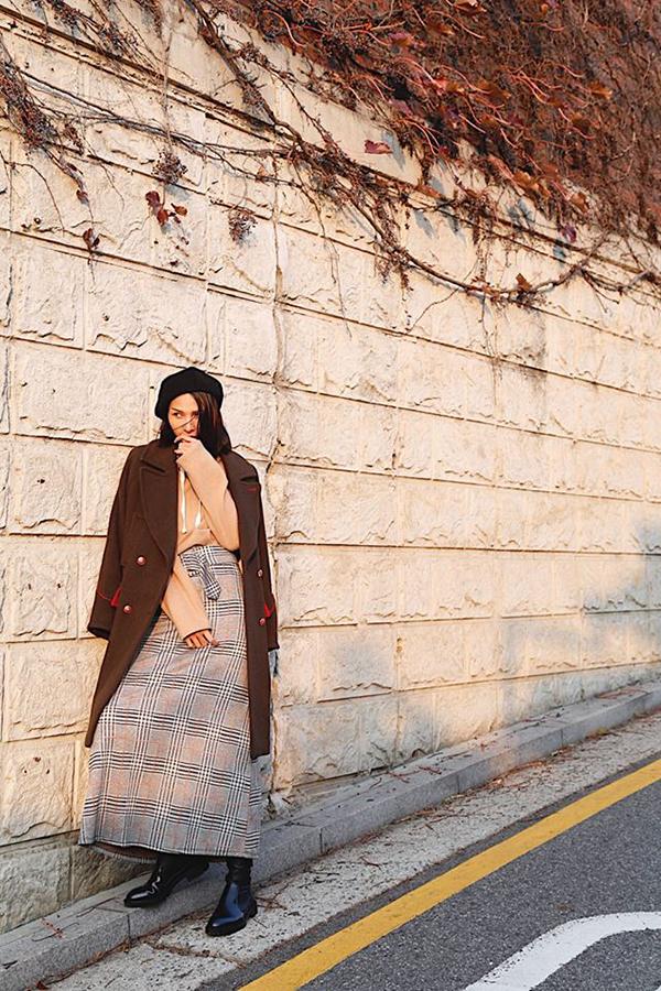 Vải in hoạ tiết kẻ sọc ca rô được thể hiện trên nhiều kiểu dáng khác nhau nhằm giúp phái đẹp thoả sức mix-match trang phục tôn nét cá tính. Minh Triệu chọn váy maxi để kết hợp cùng áo choàng mùa đông ấm áp.