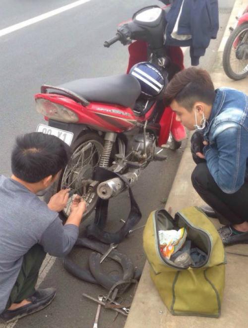 Người đàn ông tốt bụng đang thay săm giúp cho anh Hoàng. Ảnh Facebook Ma Hoàng