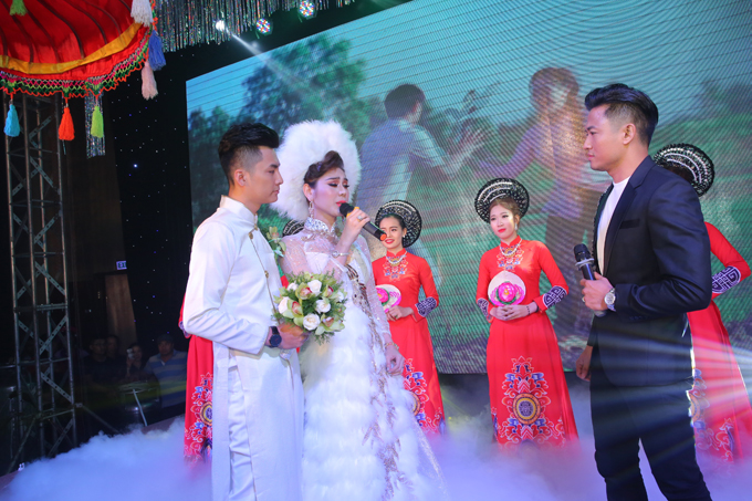 Chú rể Trần Phi Hùng thay áo dài truyền thống, sóng đôi bên cô dâu xinh đẹp trên sân khấu.