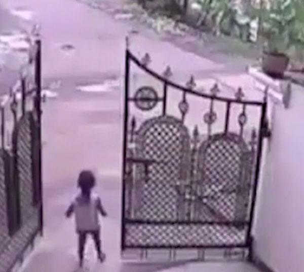 Bé gái đứng chơi một mình trước cổng, không có ai đi cùng.