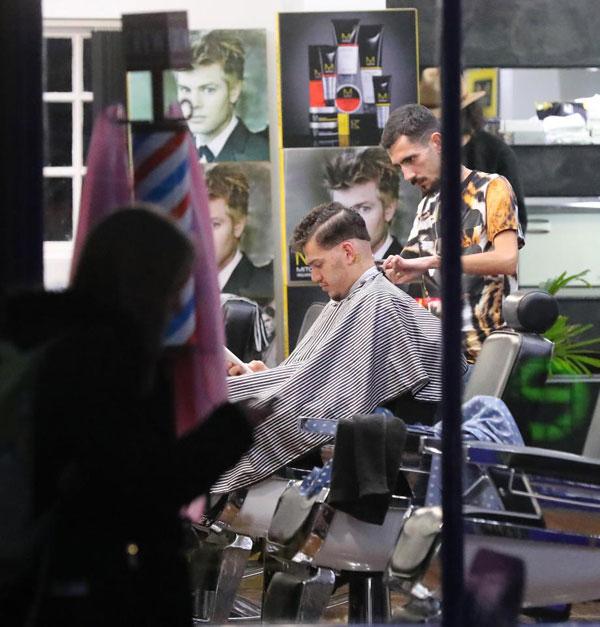 Ngôi sao 24 tuổi thảnh thơi chơi điện thoại trong khi thợ quen chăm chút cho mái tóc của mình.
