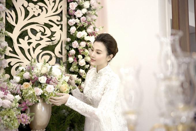 Người đẹp mặc áo dài gấm lụa trắng do nhà thiết kế Anh Thư làm riêng cho cô. Bộ lễ phục cưới được đính kết công phu, tinh xảo tôn vẻ đẹp sang trọng, quyến rũ cho cô dâu. Ngọc Duyên kiểm tra lại các khâu chuẩn bị ở nhà gái, trước khi nhà trai tới làm lễ xin dâu.