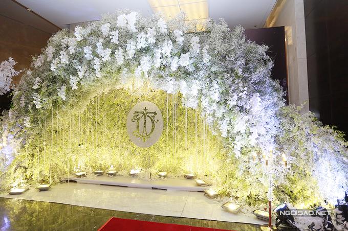 Background để cô dâu, chú rể chụp hình kỷ niệm với quan khách là cổng hoa trắng bay bổng và lãng mạn.