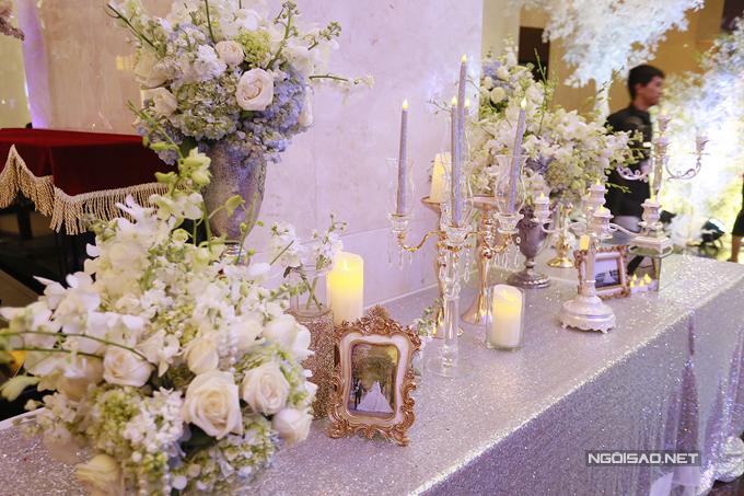 Lấy màu trắng và ánh bạc làm chủ đạo, từ hoa đến khăn trải bàn, chân nến đều toát lên vẻ sang trọng.
