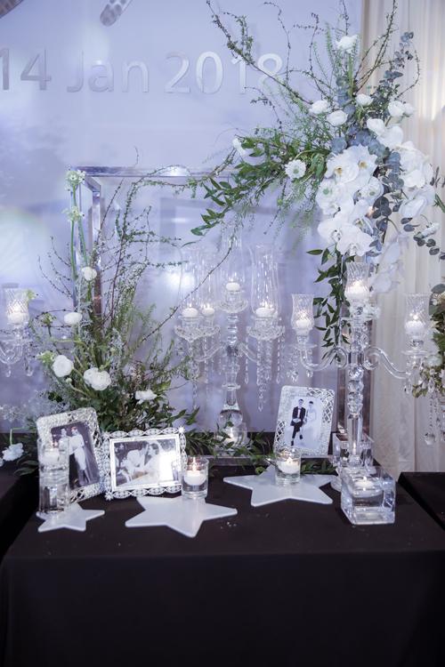 Phụ kiện được chọn lựa đi kèm là những chiếcchân nến pha lê cao cấp trên nền màu đen (vốn là màu hiếm hoi xuất hiện trong đám cưới của người Việt),tương phản với tone trắng ghi và bạc.