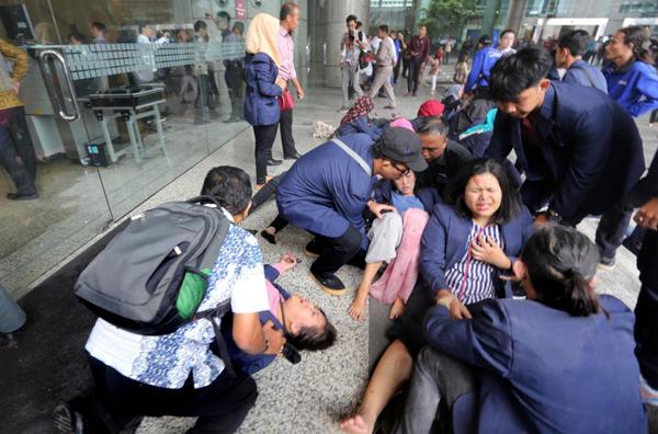 Các nạn nhân được đưa ra bên ngoài tòa nhà chờ xe cấp cứu tới. Ảnh: AP