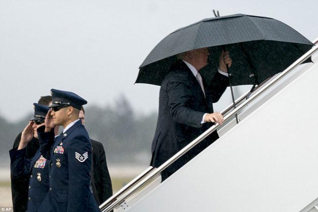 Ông Trump che ô một mình, để vợ con đầu trần trong mưa gió