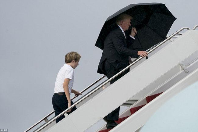 Ông Trump che ô một mình, để vợ con đầu trần trong mưa gió - 1