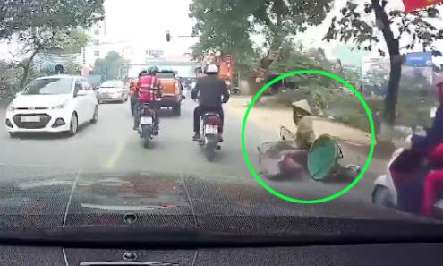 Người phụ nữ đi xe thồ ngã ra đường vì sự vô ý của một người đàn ông