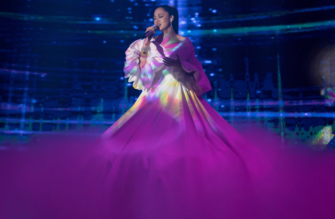 Giọng ca trưởng thành từ The Voice thể hiện ca khúc Sống xa anh chẳng dễ dàng. Chiếc váy của côđược đổi màu từ trắng sang tímngay trên sân khấu khiến khán giả bất ngờ.