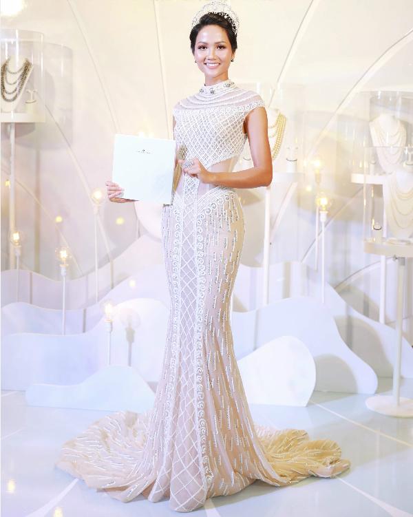 Tham dự dạ tiệc tối 14/1, Hoa hậu Hhen Niê chọn váy ren khoét lườn,thêu hoa văn đối xứng tinh tế vàôm sát cơ thể. Vương miện ngọc trai trắng và hoa tai ngọc trai đen là hai phụ kiện được người đẹp kết hợp ton sur ton với bộ trang phục thanh tú.