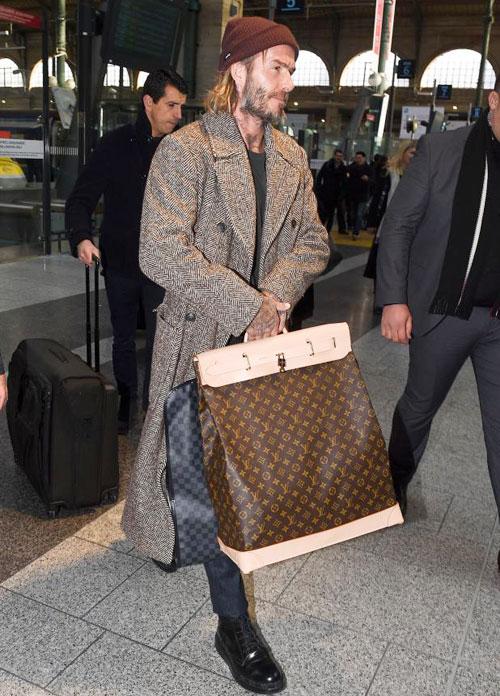 Hôm 17/1, tờ The Sun đăng tải loạt ảnh hai vợ chồng Becks tới nhà ga quốc tế St Pancras ở London để sang Paris, Pháp công tác. Becks xách hai chiếc túi to khi tới nhà ga.