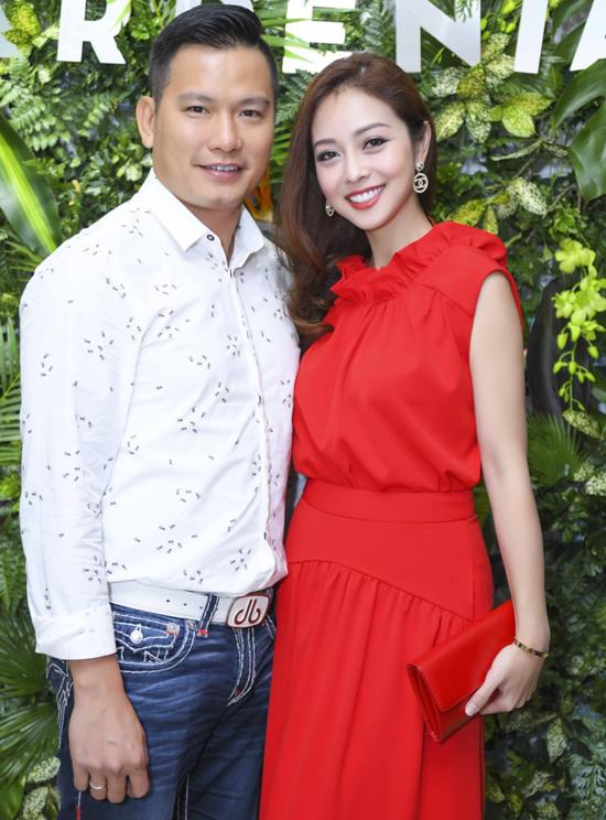 Trong khi ông xã trẻ trung với sơ mi mix quần jeans, Hoa hậu châu Á tại Mỹ 2006 lại duyên dáng với bộ đầm đỏ rực cùng clucth
