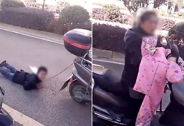 Người mẹ ngồi lái xe trong khi con trai gào khóc vì bị kéo lê dưới nền đường ở phía sau.