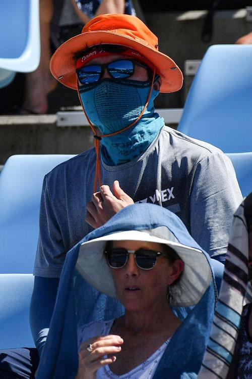 CĐV trên sân đội mũ mịt mặt kín mít để tránh nắng.