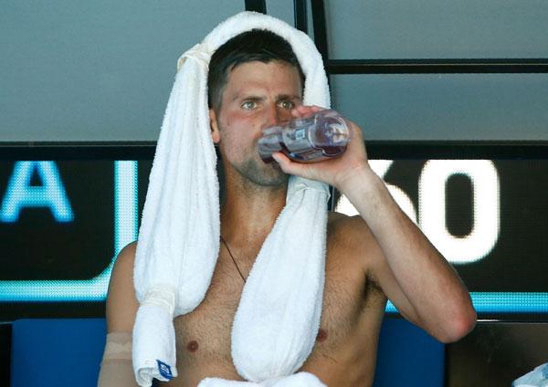 Tay vợt cựu số một thế giới quàng khăn lạnh, uống nước liên tục trong giờ nghỉ.
