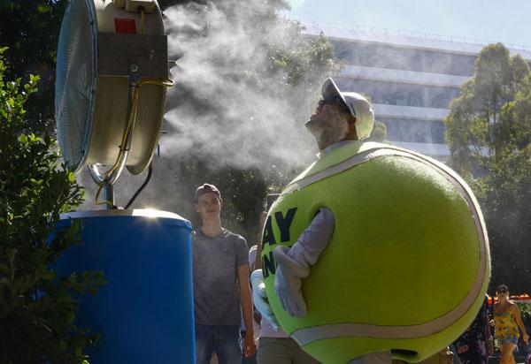 Nhân viên phục vụ giải đấu cũng tìm tới góc để quạt hơi nước để giảm nhiệt.