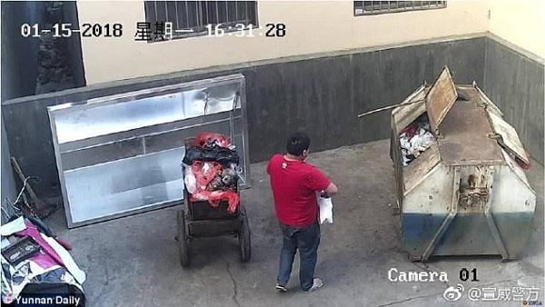 Li bế con ra thùng rác rồi vứt bỏ. Ảnh: Yunnan Daily