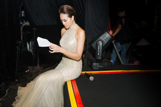 Chân dài ngồi bệt ở sàn sân khấu đọc lại kịch bản trước khi chương trình diễn ra.