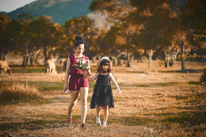 Thuý Nga nắm tay con gái Nguyệt Cát đi chơi ở đồng cỏ.