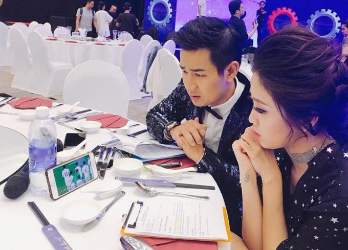 MC Nguyên Khang và Liêu Hà Trinh cùng theo dõi loạt đá luân lưu trên điện thoại trong lúc