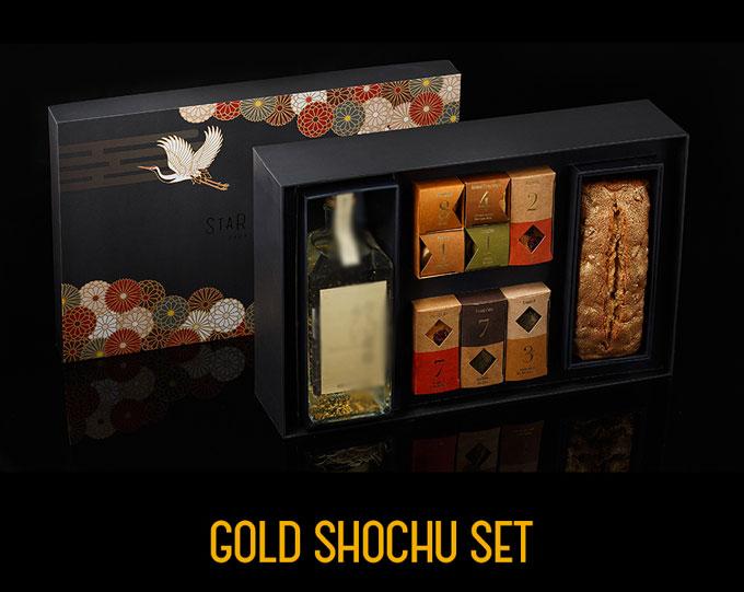 Star Kichen - hộp quà tặng Vàng Shochu được gói trong hộp giấy nghệ thuật cao cấp họa tiết hạc xuân, nổi bật với sản phẩm rượu Shochu có bột vàng và bánh Golden Fruit Pound Cake phủ vàng.