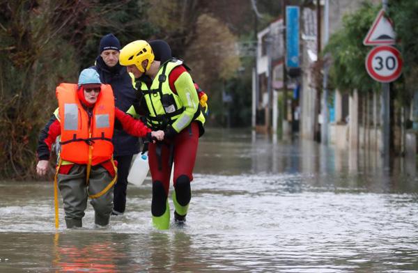 Một cụ bà được thợ lặn của đội cứu hộ thành phố giúp đỡ sau khi cụ đi bộ giữa đường ngập nước về nhà để cho các con vật nuôi ăn.