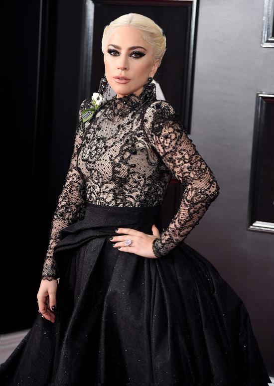 Gaga cài trên váy bông hoa trắng - hình ảnh biểu tượng cho chiến dịch Times Up chống nạn lạm dụng tình dục.
