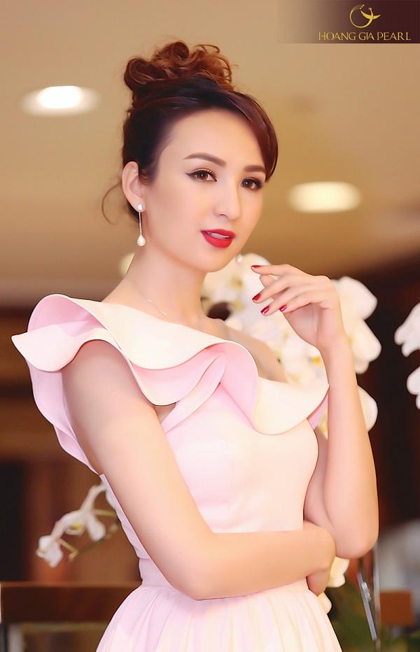Trang sức dáng dài kết hợp với chiếc đầm hồng nữ tính giúp Hoa hậu Ngọc Diễm thêmtrẻ trung, duyên dáng.