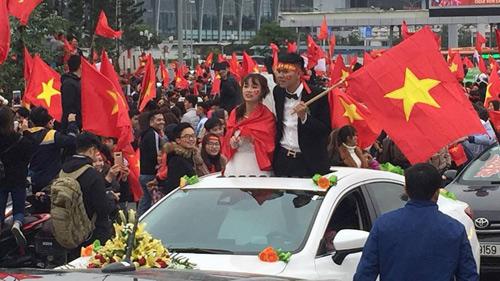 Cặp đôi thay vì trở về nhà trai lại cầm cờ cổ vũ nhiệt tình.