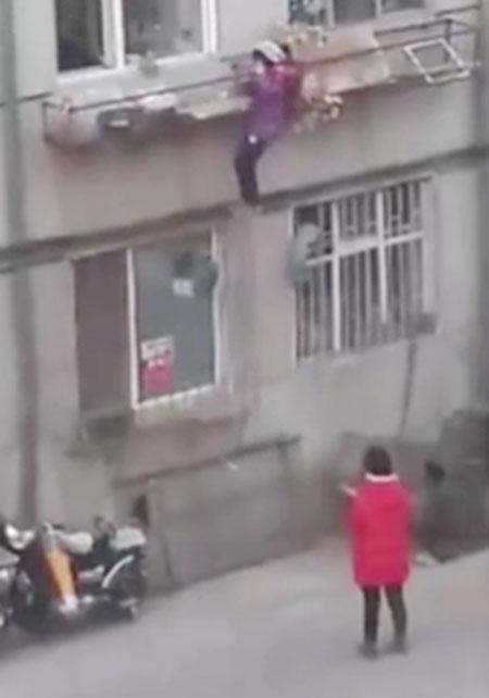 Bé gái đu bám khó khăn để trèo lên.