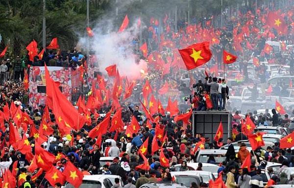 Fan Việt Nam vẫy cờ tổ quốc khi xe bus chở đội bóng