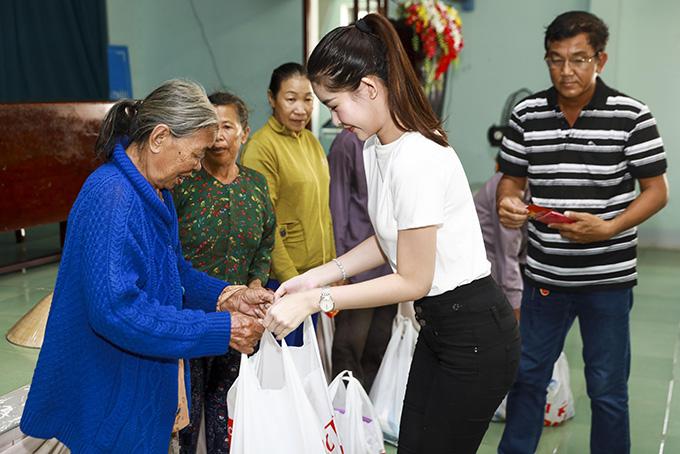 Ngân Anh và bố cùng đại diện Uỷ ban nhân dân xã trao quà cho các gia đình nghèo.