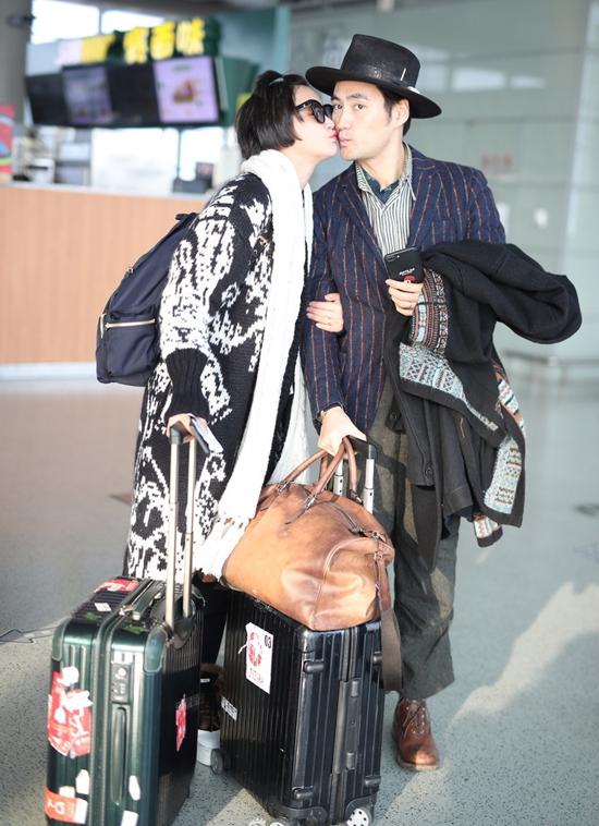 Cặp sao mang theo rất nhiều vali đồ áo, dường như họ vừa trải qua một chuyến đi dài. Dù vậy, thần sắc hai vợ chồng đềuvui vẻ, rạng rỡ. Thi thoảng, Trương Hâm Nghệ quay sang ôm hôn chồng tình tứ.