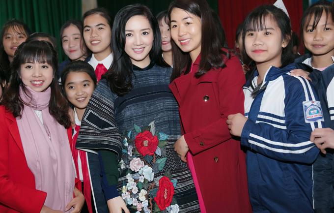 Người đẹp diện áo dài thổ cẩm thêu hoa, chụp ảnh cùng các em học sinh.