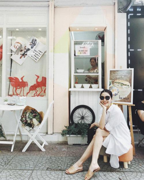 Tăng Thanh Hà diện trang phục đơn giản, không ngần ngại ngồi lề đường ăn bánh mì bình dân.