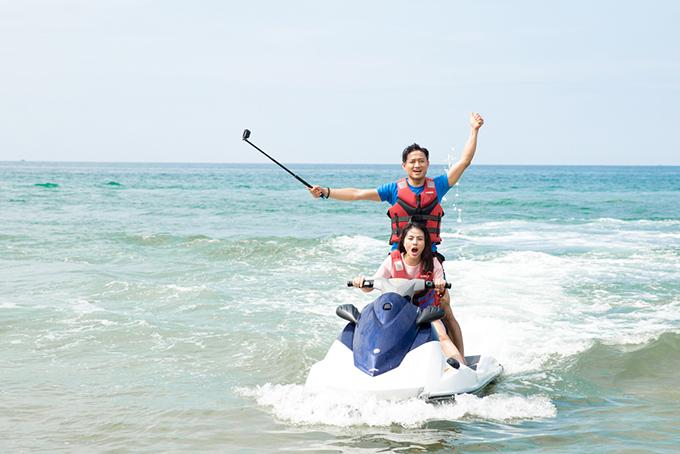 Vân Trang cầm lái chiếc mô tô, chở Quý Bình lướt sóng.