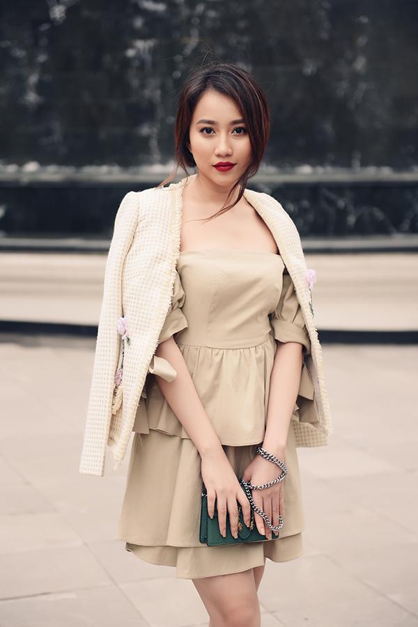 Áo khoác vải tweed ngoài hoạ tiết kẻ sọc ca rô nhí xinh xắn còn được trang trí hoa thêu ruy băng tô đậm nét nữ tính cho người sử dụng.