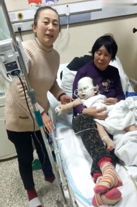 Cậu bé Junjie đang được bà và mẹ chăm sóc trong bệnh viện. Ảnh: AsiaWire
