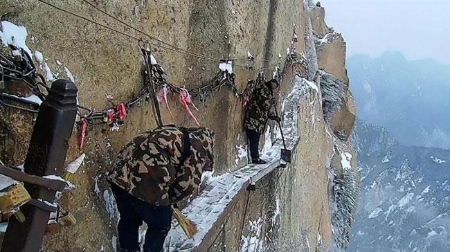 Nhóm công nhân dùng xẻng và chổi dọn tuyết.