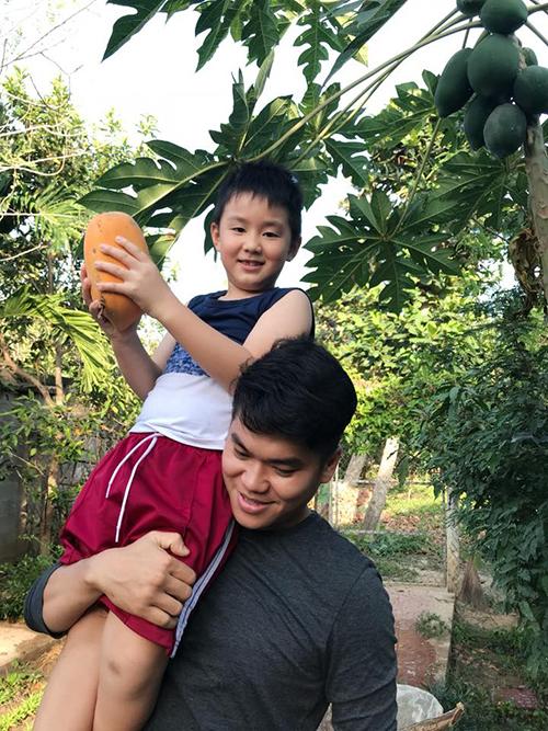Con trai Lê Phương thân thiết với cha dượng. Trung Kiên bế bé trên vai vào vườn hái đu đủ.