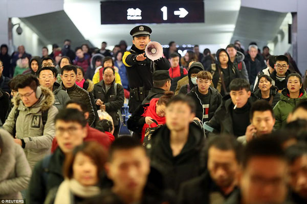 A policeman keeps order at Yuncheng North railway station in Chinas Shanxi Province today as travellers pack the space